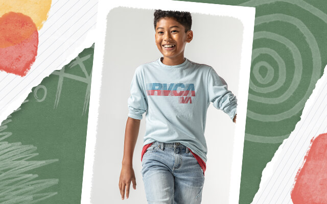 A boy wearing a pink graphic tee over a black long sleeve tee and light wash jeans. A boy wearing a blue RVCA long sleeve tee and light wash jeans.