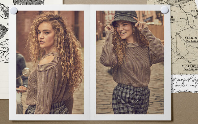 A gal walking down the street wearing a grey bucket hat, a brown cold shoulder sweater and a pair of black and grey plaid pants.