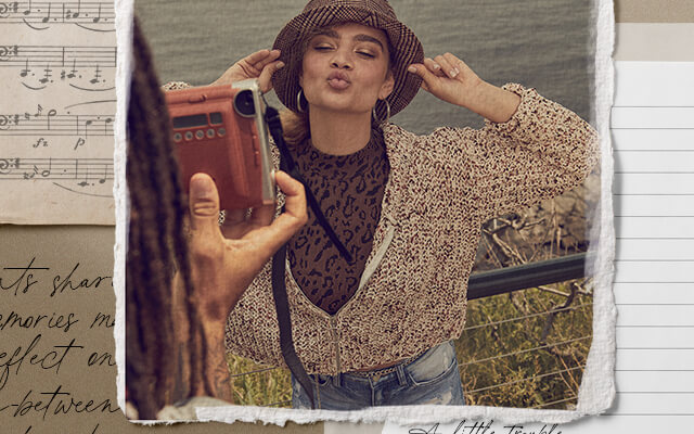 A gal wearing a brown cardigan over a brown animal print tank and light wash denim.