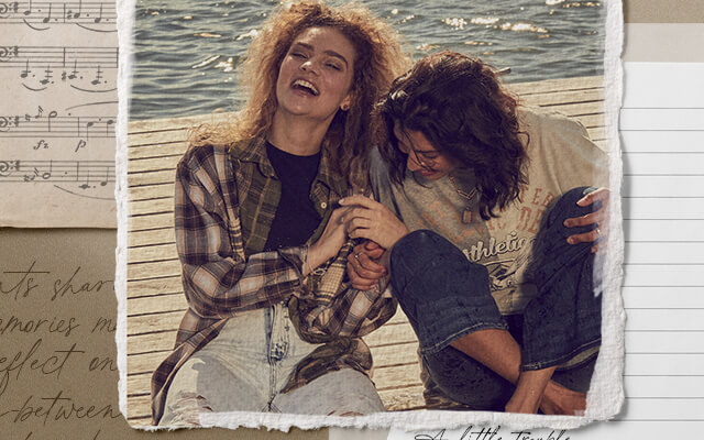 Two girls sitting on a dock wearing a blue and cream flannel shirt and light wash jeans and another gal wearing a grey and cream graphic tee with dark wash denim.
