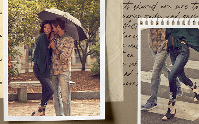 A gal wearing a green blouse with a pair of dark washed destructed denim. A guy wearing a yellow and grey plaid shirt with a pair of light wash destructed denim walking under an umbrella.