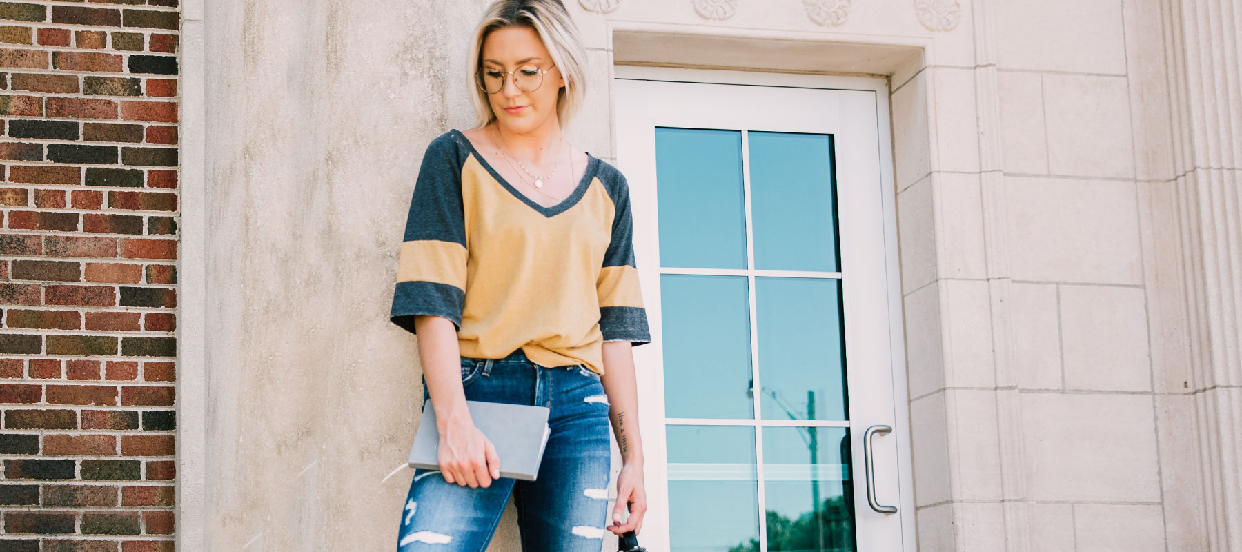 Girl standing in front of school, wearing yellow colorblock tee and glasses from Buckle's campus shop collection.