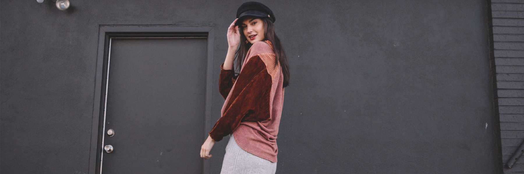 Girl wearing a burgundy top and a black hat in front of a dark grey wall