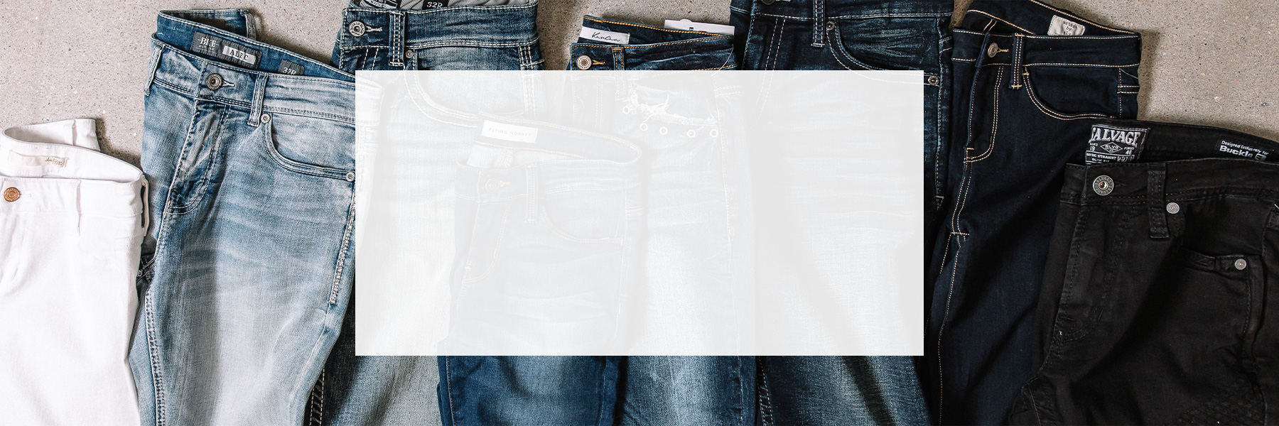 Seven pairs of denim that range from light colored wash to dark colored wash.