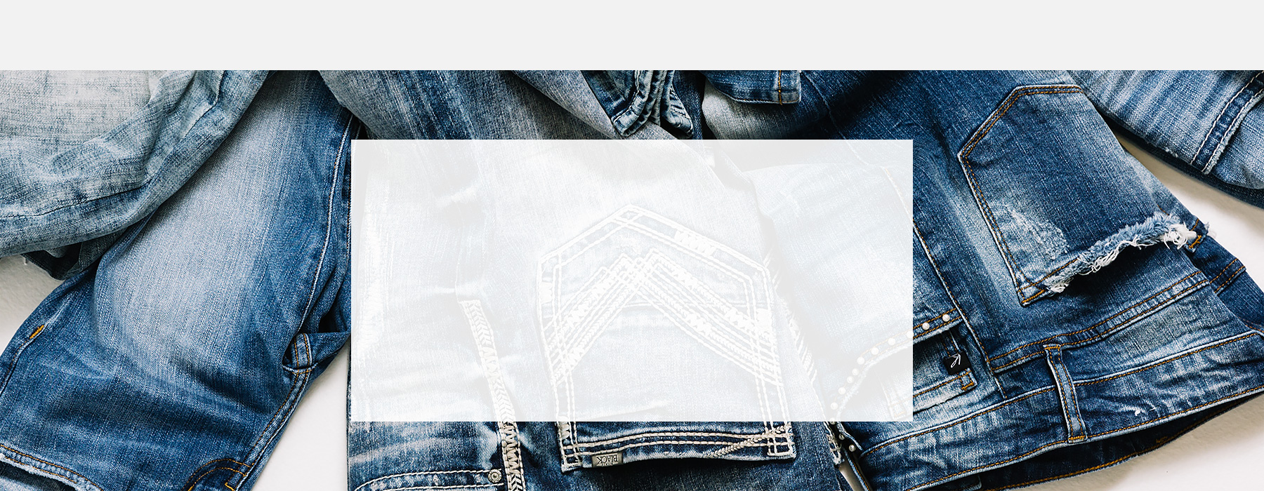Men's and women's jeans spread out on white background.