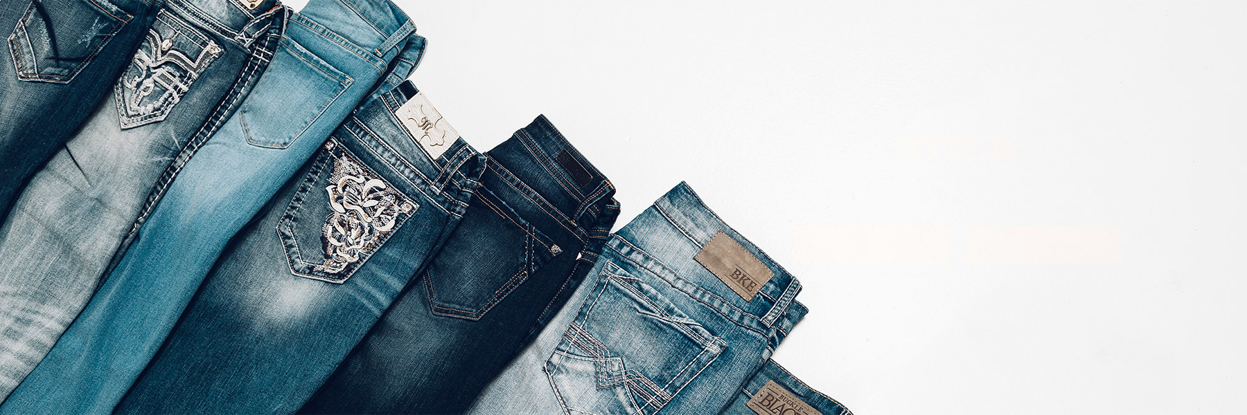Assorted new styles of jeans from Buckle, folded to show back pocket details, laying on white background.