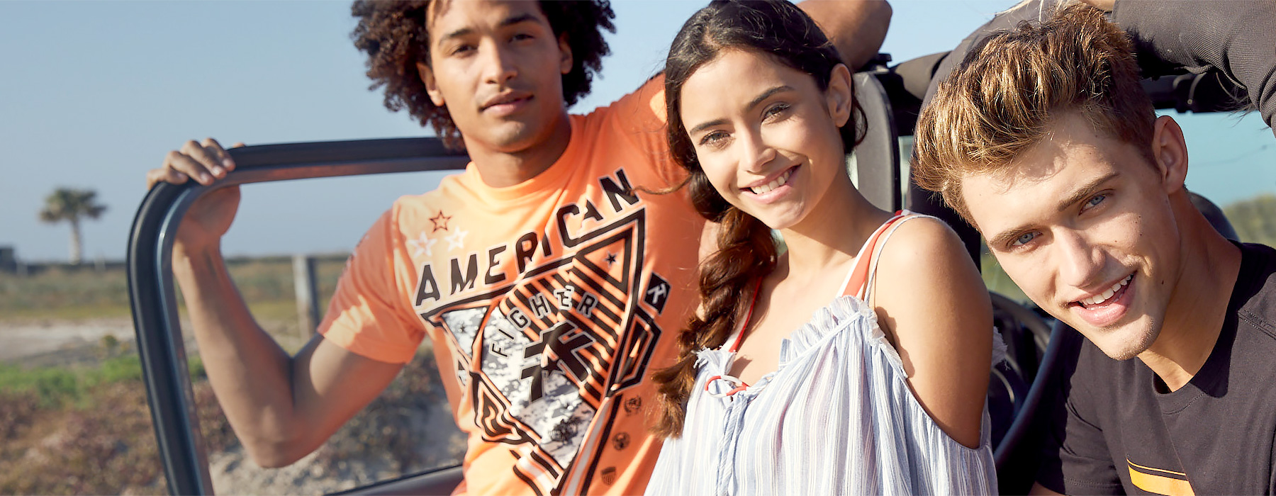 Guy wearing an orange American Fighter short sleeve t-shirt. Girl wearing a blue cold shoulder top and guy wearing a black short sleeve t-shirt.
