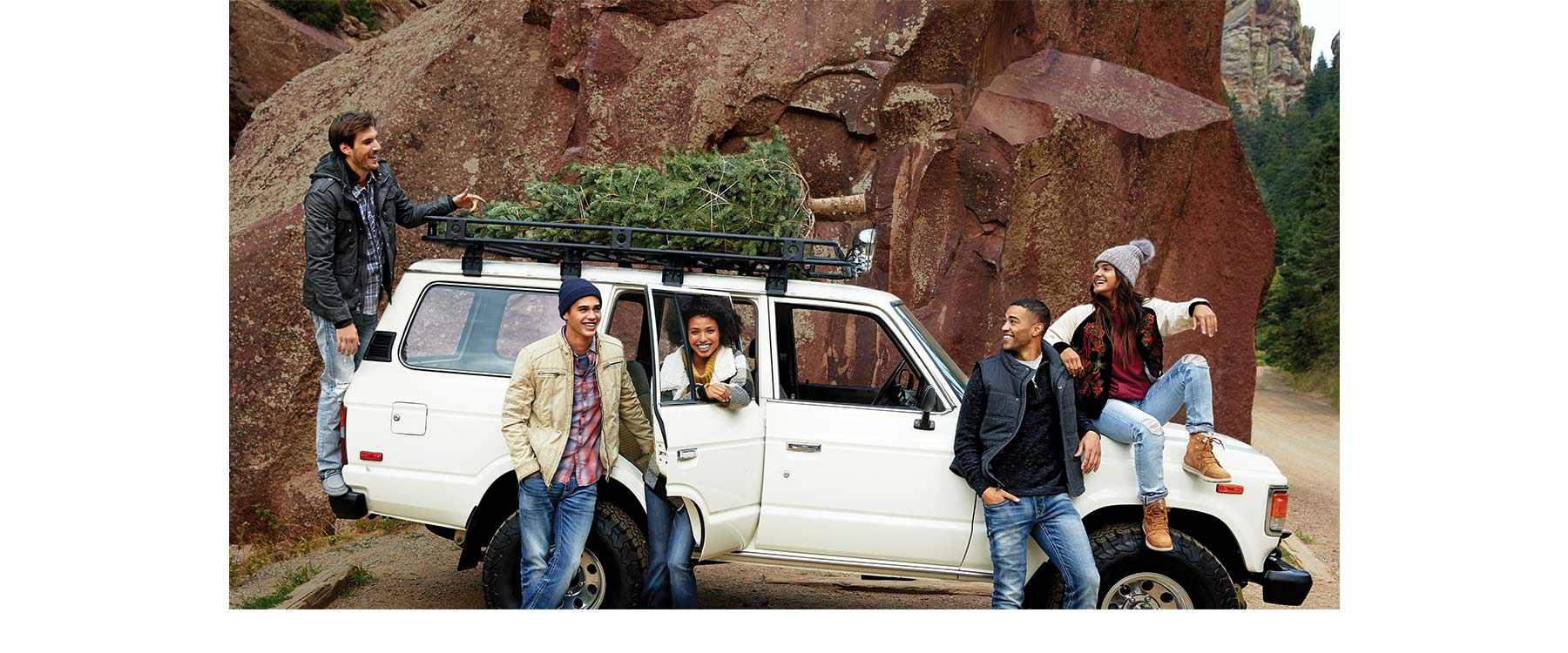 Group of people sitting on and around jeep, hauling a tree on top. All wearing outfits from Buckle's winter collection.