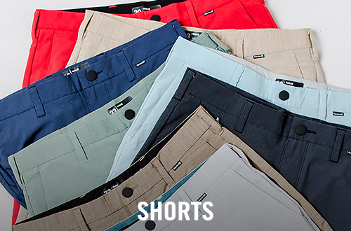 Eight different pairs of men's shorts lying on top of each other