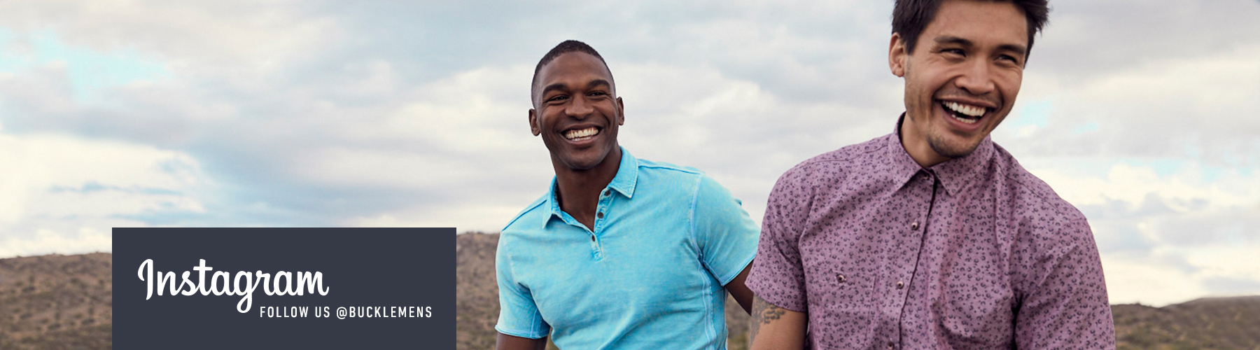 Two guys laughing, one wearing a blue BKE polo, and the other one wearing a purple, printed, button-up shirt.