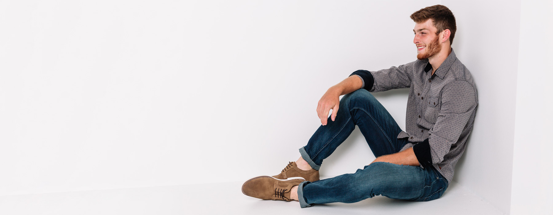 Guy sitting against white wall with hand on his knee, wearing dark wash denim from Buckle.