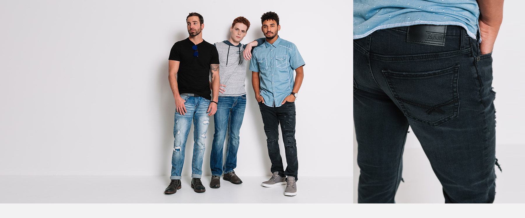 A guy wearing a pair of light wash distressed denim with a black tee. Another guy wearing a grey hooded t-shirt with dark denim. Guy wearing a blue button down shirt with black destructed denim.