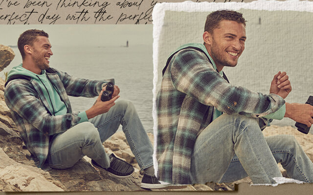 A guy sitting on rocks wearing a pair of light wash denim with a blue, teal, and cream plaid shirt over a teal hoodie.