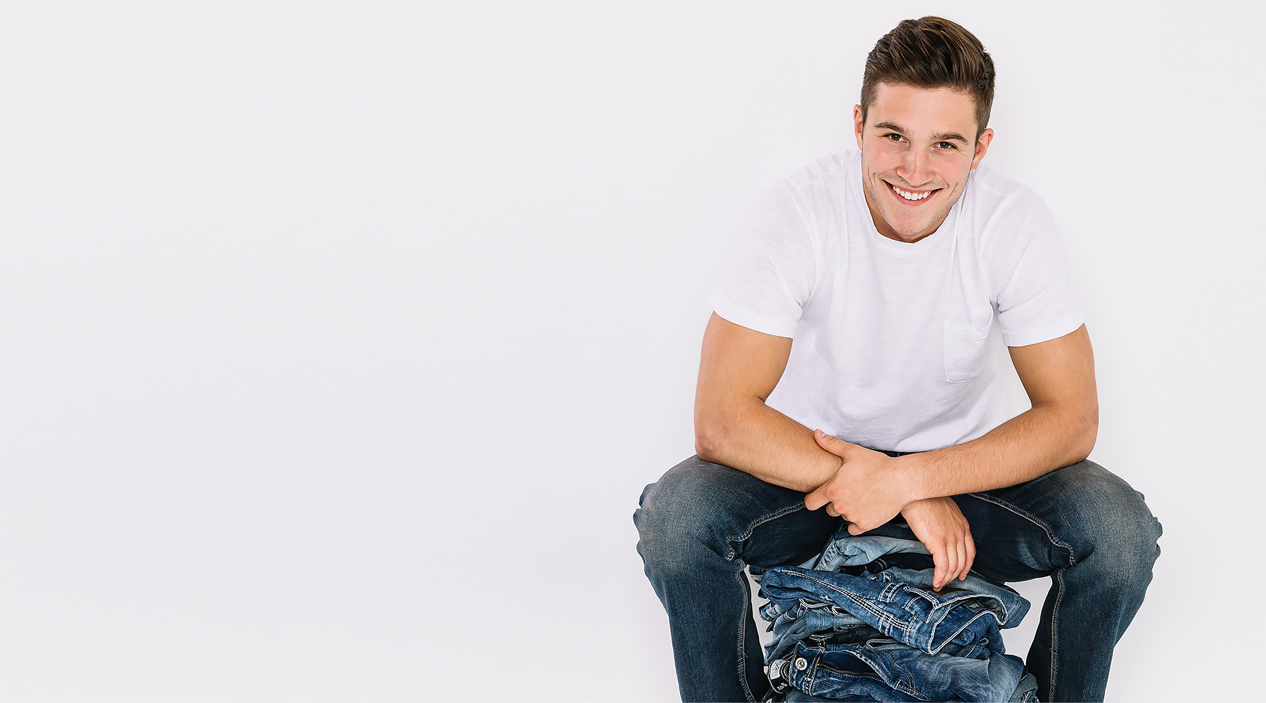 Guy wearing a white short sleeve basic tee and dark wash denim siting on top of a pile of denim