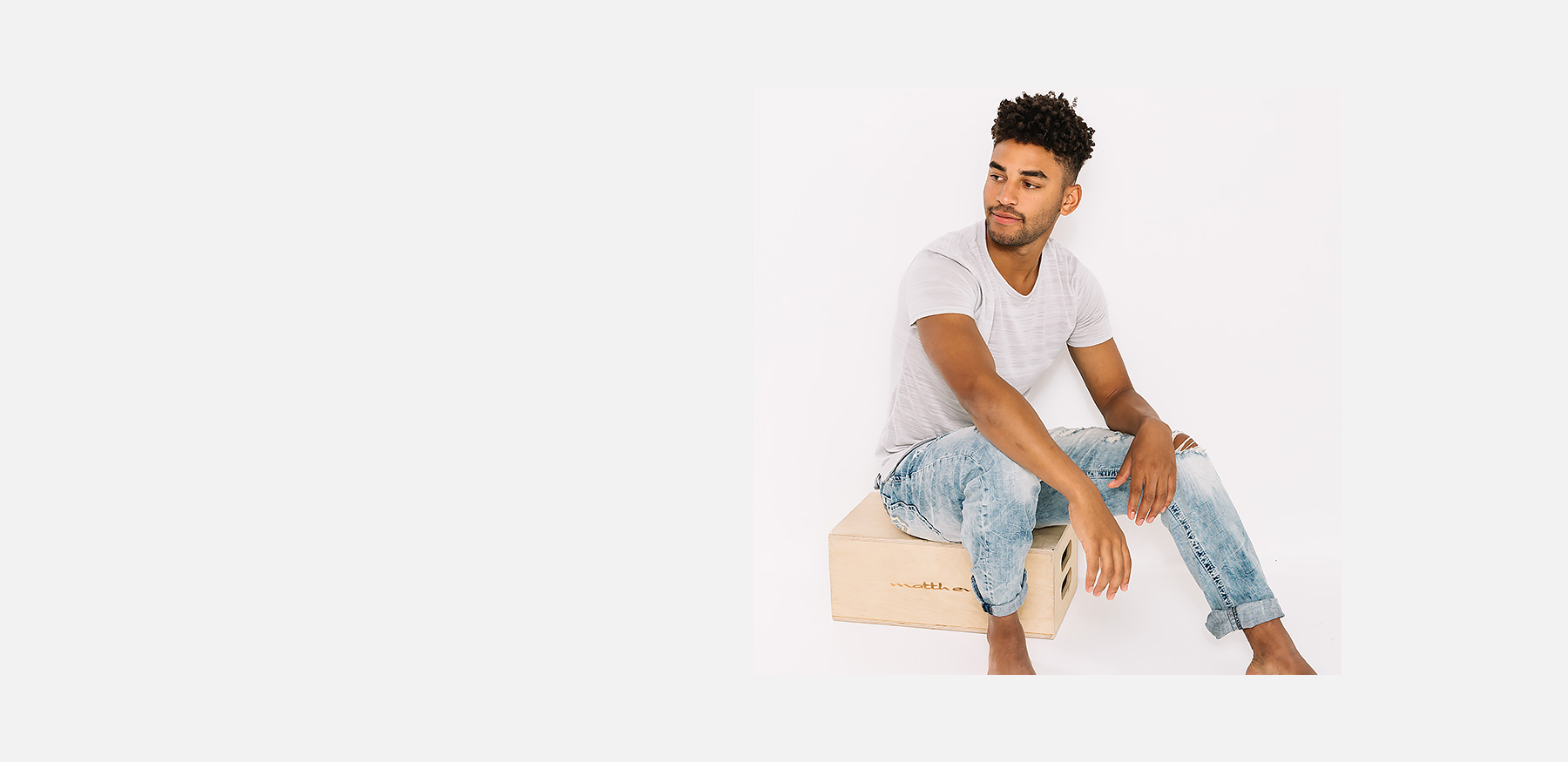 Guy sitting on a wooden box wearing a grey tee and light washed denim