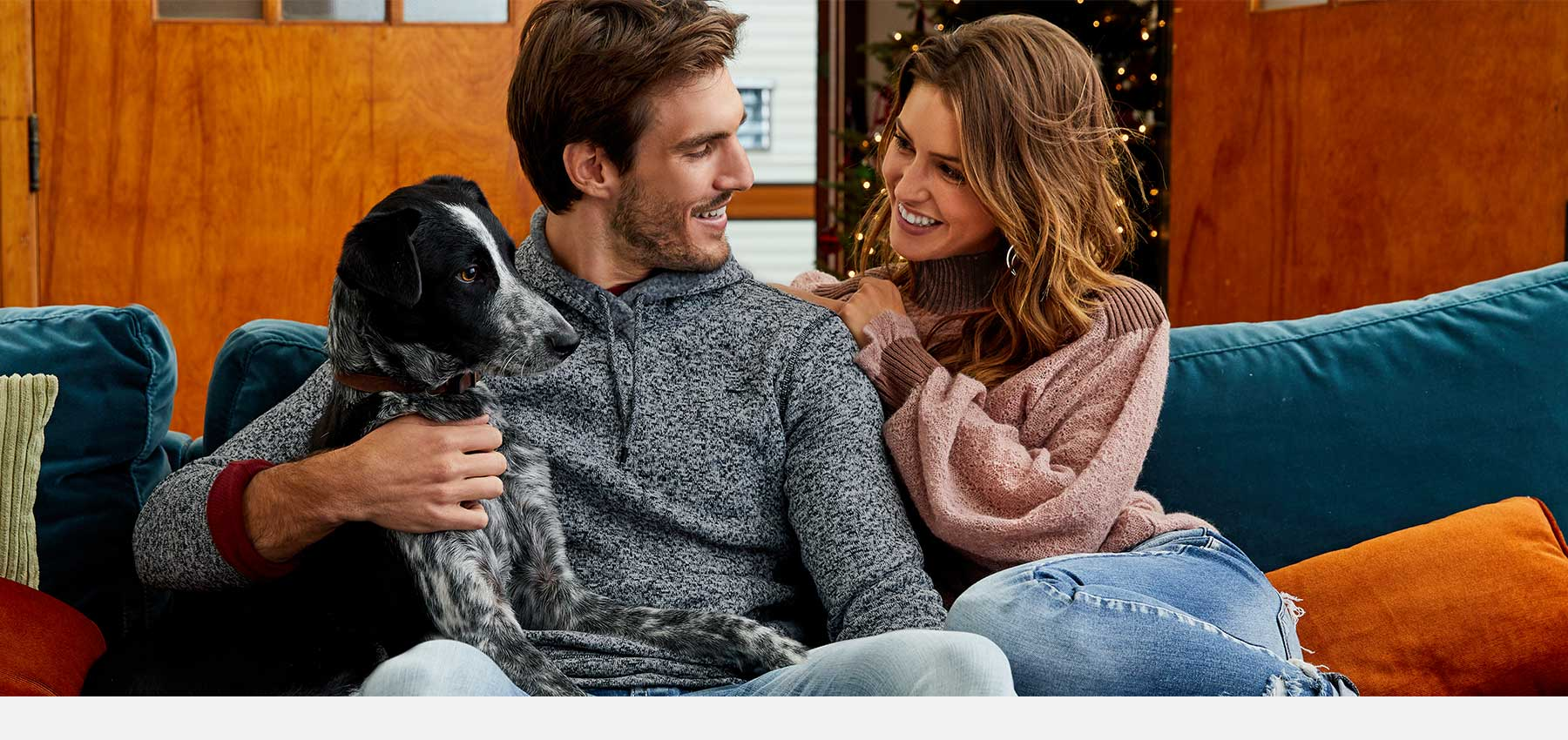 Couple sitting on a couch the their dog, bot wearing outfits from Buckle's holiday launch.