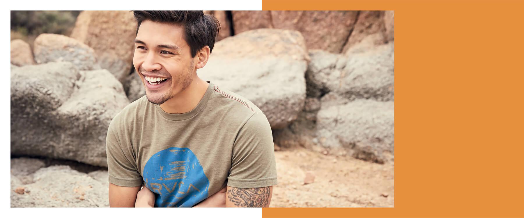 Man wearing a khaki RVCA short sleeve t-shirt