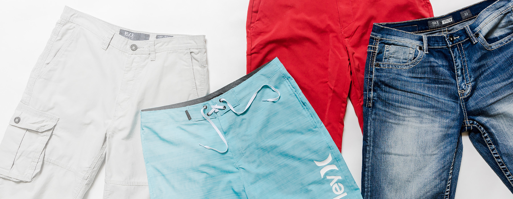 A pair of BKE khaki shorts, a pair of Hurley boardshorts, and a pair of BKE denim shorts