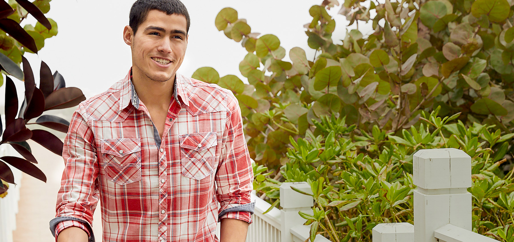 Guy wearing a red and white long sleeve plaid button up shirt in front of green scenery