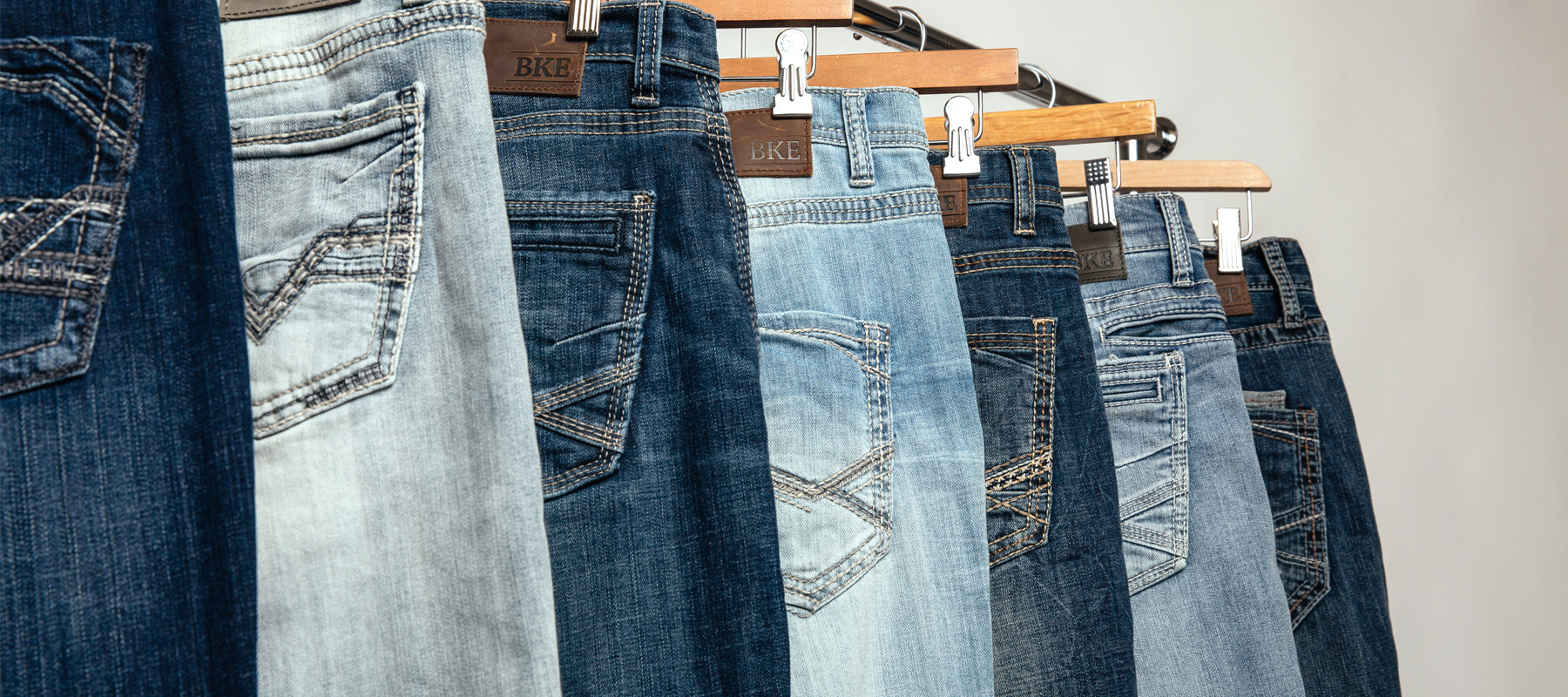 Different washes of jeans overlapping each other to show the wash and back pocket detail.