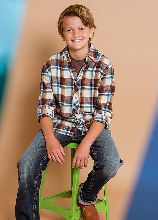 Little boy sittings on a stool smiling and wearing a Fall outfit from Buckle.