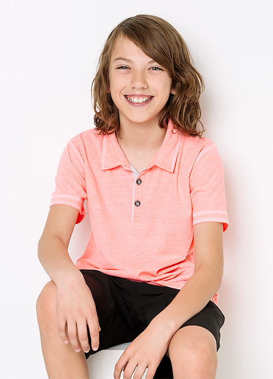 Little boy wearing BKE polo and black shorts from Buckle.