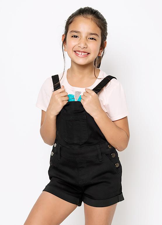 Little girl wearing black shortalls from Buckle.