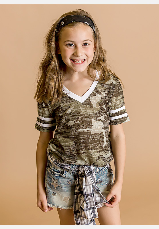 Little girls wearing a green camo short sleeve t-shirt with Buckle denim shorts