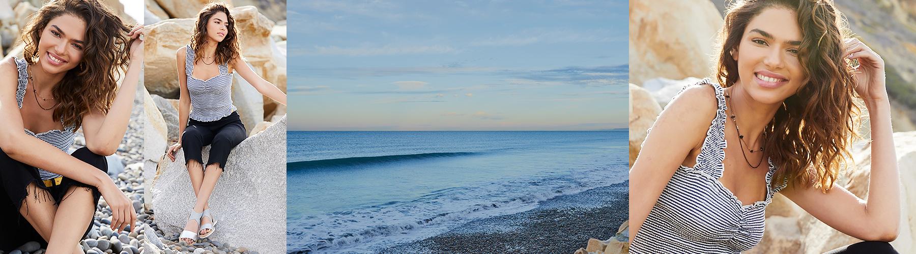 Smiling girl sitting on rocks by ocean wearing Billabong Sun Dreamer striped tank top and black jeans.