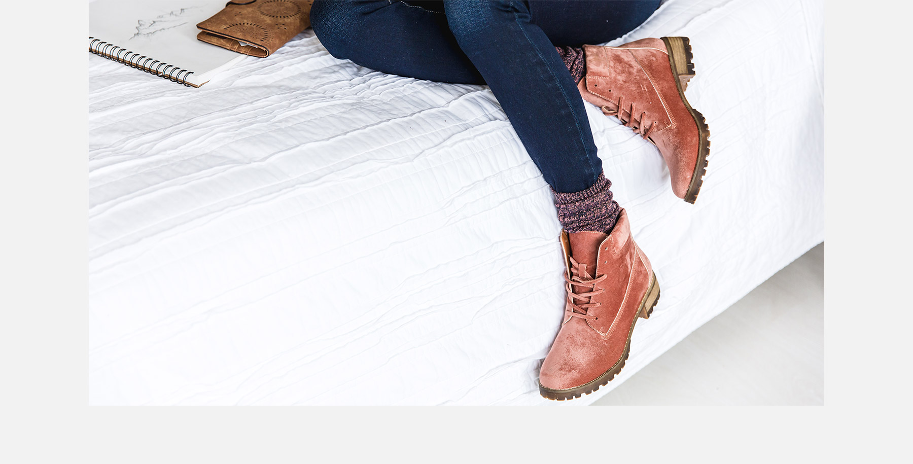 Girl sitting on a bed wearing a pair of dark wash denim with pink socks and a pair pink lace up boots