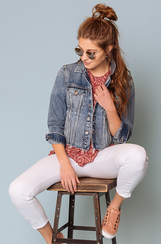 Girl wearing a red blouse with a denim jacket and white denim and pink sneakers with sunglasses