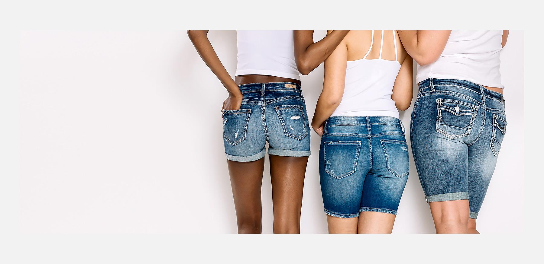Three girls wearing white tanks and tees and denim shorts