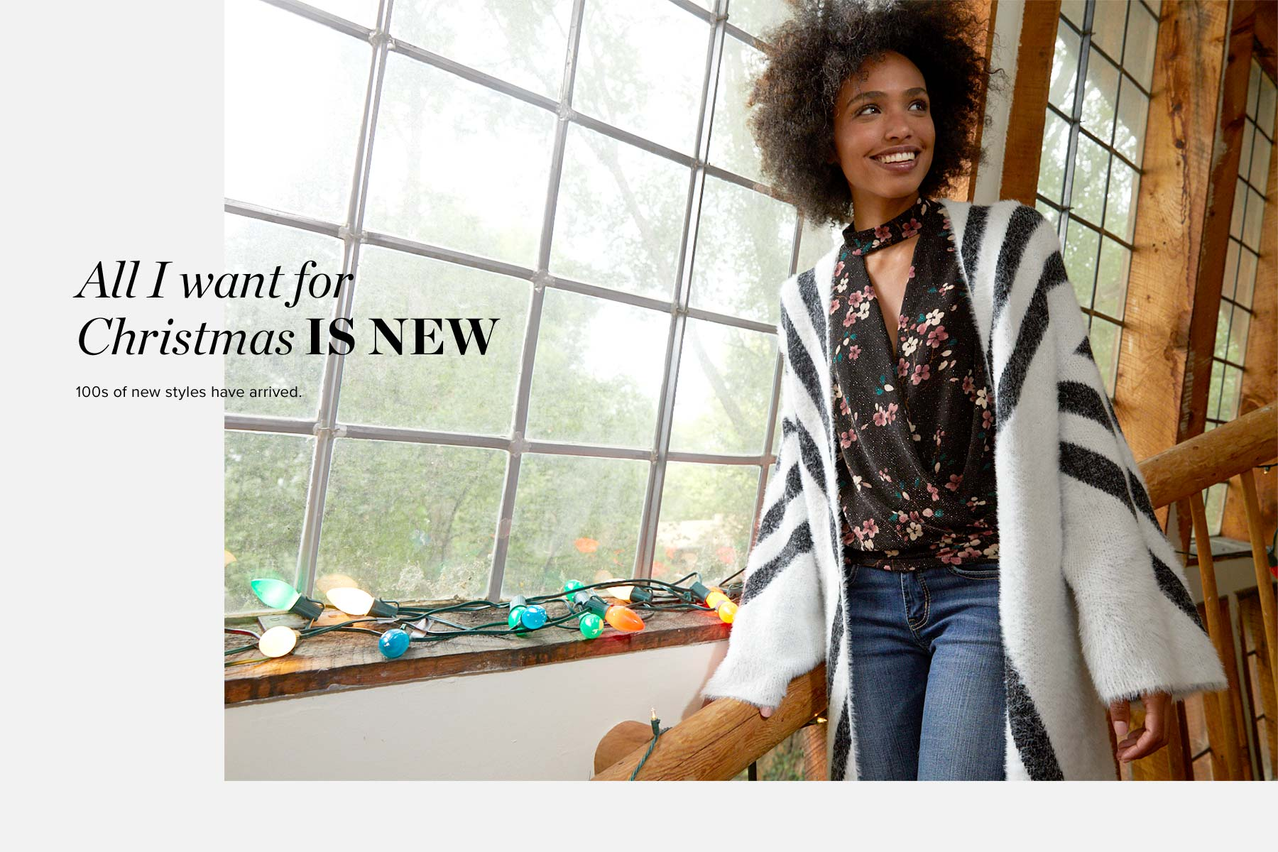All I Want For Christmas IS NEW - 100s of new styles have arrived. Girl wearing a black floral blouse with a white and black striped cardigan and dark wash jeans