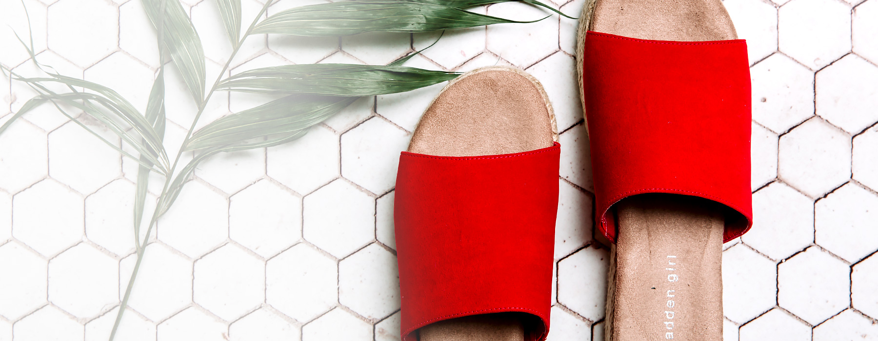 A pair of red sandals on a tile floor