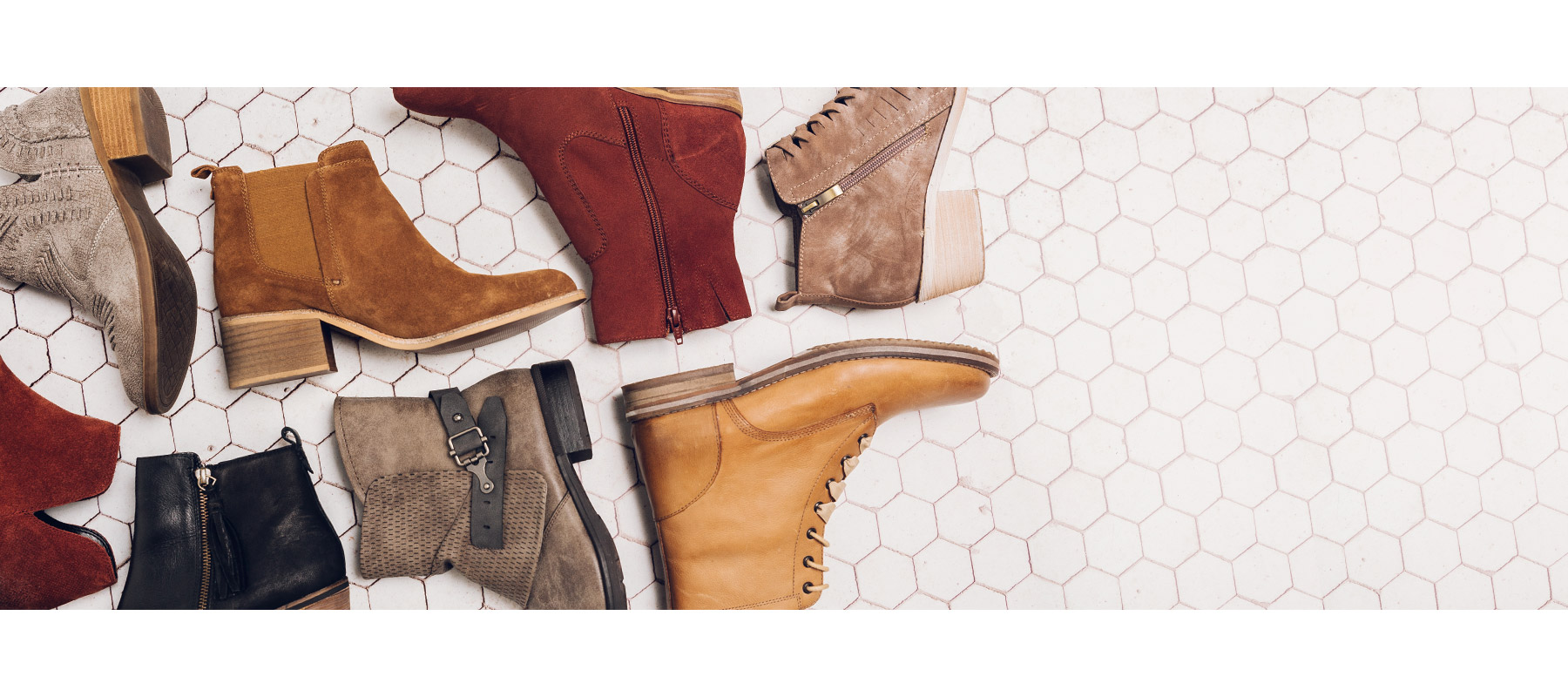 Assorted new styles of women's boots from Buckle's fall collection, laying on tiled floor.