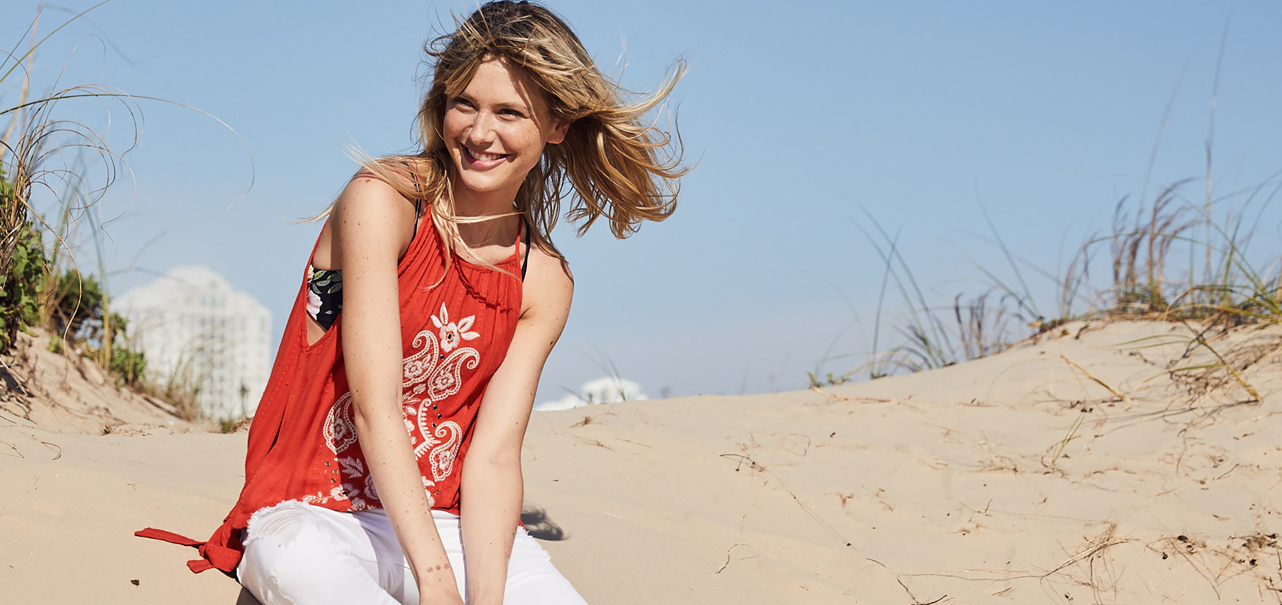 Girl wearing a red embroidered tank with white denim bottoms on a beach